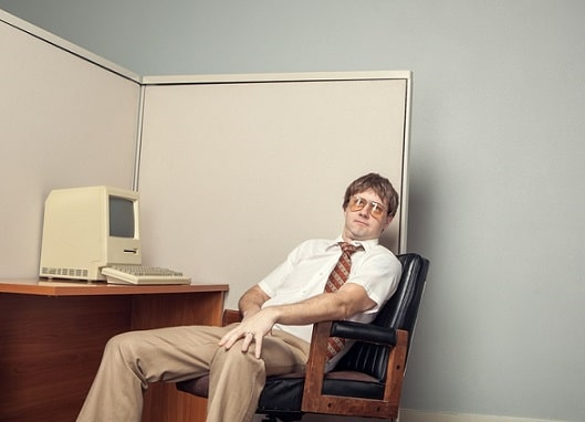 A lazy I.T. computer technician leans back in his chair in his office cubicle sitting in front of his desk with a vintage 1980s computer. Horizontal with copy space.