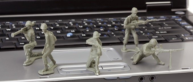 An open laptop computer isolated on a white background guarded by plastic toy soldiers. Photo has a shallow depth of field.